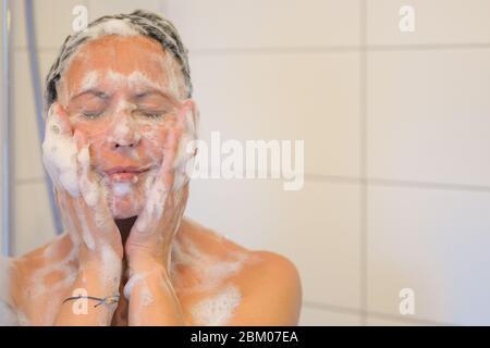 Eine glückselige Frau mittleren Alters genießt eine Dusche, die ihr Gesicht mit ihren Händen an ihre Wangen und geschlossenen Augen mit einem ruhigen Lächeln einseift - Stockfoto
