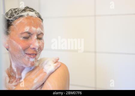 Glücklich hispanische Frau lächelnd, wie sie genießt eine Dusche in Seife suds bedeckt - Stockfoto