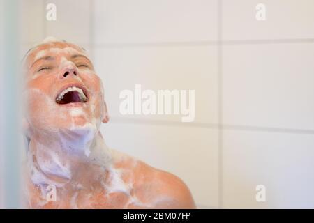 Glückliche hispanische Frau lacht, als sie eine Dusche mit Seifenlauge bedeckt mit ihrem Gesicht zum heißen Wasser von oben angehoben genießt - Stockfoto