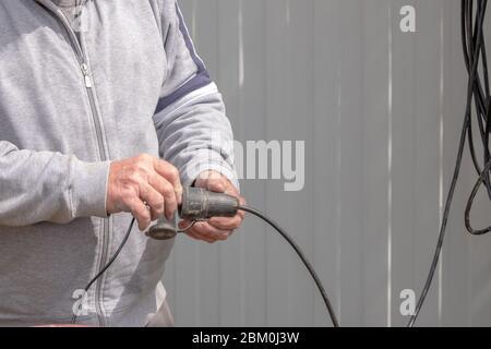 Die Männer eines Arbeiters halten ein schwarzes Stromkabel. Sonniger Tag. Der Draht ist verschmutzt und spricht über seine häufige Verwendung. - Stockfoto