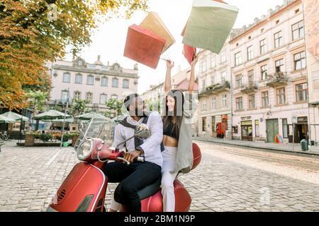 Charmante lächelnde kaukasische Frau sitzt hinter ihrem schönen afrikanischen Freund auf dem roten Roller mit Shop Taschen in ihren Händen auf der angehoben - Stockfoto