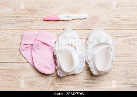Schwangerschaftstest mit positivem Ergebnis und Kleidung für Neugeborene, kopieren Raum für Text. Erweiterung Familie Konzept Draufsicht auf Holztisch. - Stockfoto