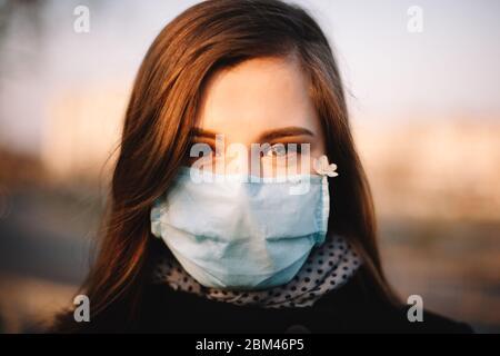 Porträt von glücklichen Teenager-Mädchen mit Schutzgesicht medizinische Maske im Freien auf der Straße der Stadt im Frühjahr - Stockfoto