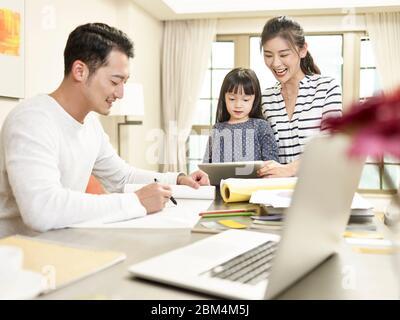 Junge asiatische Familie mit einem Kind zu Hause glücklich und fröhlich (Kunstwerk im Hintergrund digital verändert) - Stockfoto