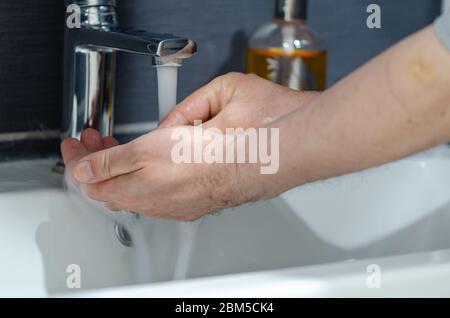 Der Mann wascht seine Hand mit Seife, um vor der Coronavirus-Pandemie zu schützen - Stockfoto