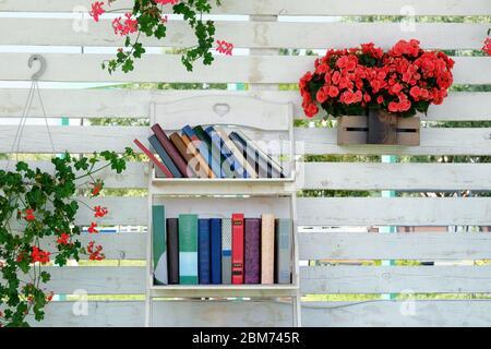 Buch Stapel von Schritt zum Erfolg Konzept, blühende Pflanzen in Töpfen auf Hintergrund. Vintage-Bücher mit leeren Etiketten mit kostenlosem Kopierplatz auf einem weißen Regal. Stockfoto