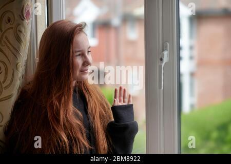 Seitenansicht des glücklichen Rotschopf Teenager-Mädchen in Freizeitkleidung mit langen Haaren stehen neben dem Fenster winken Hand zu Freund nebenan, während Blick aus dem Fenster - Stockfoto