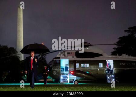 US-Präsident Donald Trump geht mit einem Regenschirm von Marine One aus zurück ins Weiße Haus, nachdem er am 5. Mai 2020 in Washington DC nach Phoenix gereist ist. - Stockfoto