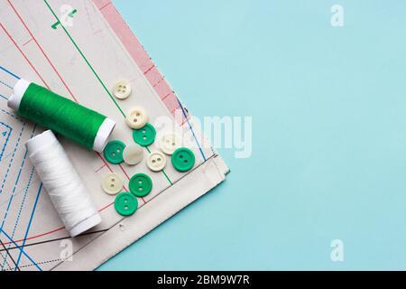 Papiermuster, Fäden und Knöpfe auf blauem Hintergrund, Nahaufnahme, Kopierbereich. - Stockfoto