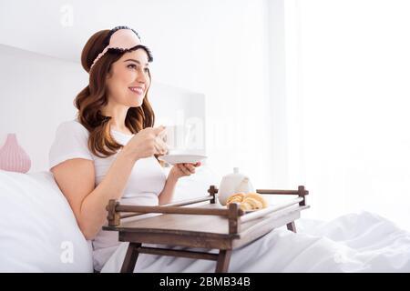 Profil Seitenansicht Porträt von ihr sie schön attraktiv schöne fröhlich rothaarige Mädchen sitzt im Bett essen Mittagessen Fernsehen in modernen weißen Licht - Stockfoto