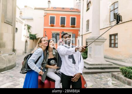 Multiethnisch glücklich junge Menschen, Afrikaner und zwei kaukasische Mädchen, machen Selfie Foto mit lustigen lachenden Gesichter, im alten Stadthof wi stehen - Stockfoto