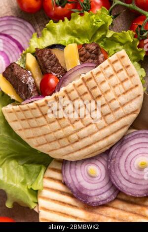 Döner Kebab Pita mit grünem Salat, Tomaten Kirsche, Kartoffel frei, gegrilltes Rindfleisch in der Lunchbox auf Wrap Hintergrund - Stockfoto