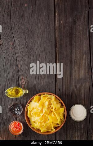 Pappardelle Pasta mit Lachs. italienische traditionelle Küche. Fertige Zutaten auf einem Holztisch mit Kopierraum. - Stockfoto