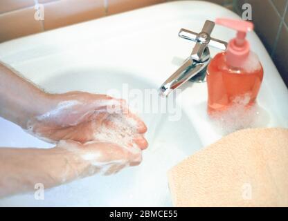 Mann, der sich die Hände wäscht. Häufiges Händewaschen wird empfohlen, um das Risiko der Ausbreitung von Covid 19 oder Coronavirus im Jahr 2020 zu verringern - Stockfoto