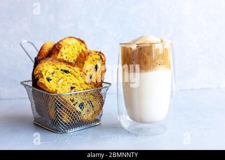 Tasse trendy Schlagsahne kalten Dalgona Kaffee und italienischen Biscotti auf hellgrauen Hintergrund. - Stockfoto