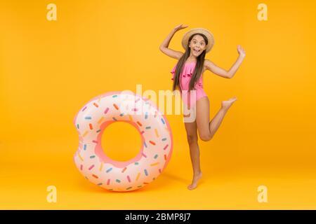 Erste goldene Bräune. Kleines Mädchen gehen, um im Wasser zu spielen. Spaß am Strand. Glückliches Kind am Sommerstrand. Entspannen Sie sich im Meer. Spaß im Wasserpark. Mädchen mit aufblasbarem Gummiring am Schwimmbad. - Stockfoto