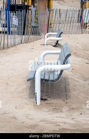 Ein geschlossener Strand bedeckt fast hölzerne Parkbänke, durch einen eingezäunten Spielplatz, während covid-19 geschlossen in Michigan USA - Stockfoto