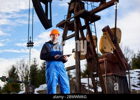Porträt des Petrolium-Ingenieurs in blauen Overalls und orangenen Helm, mit Laptop, mit dem Rücken zu einer Ölplattform stehend, die Ölpumpeinheit prüfend, Notizen in seinem Computer machend, lächelnd zur Kamera. - Stockfoto