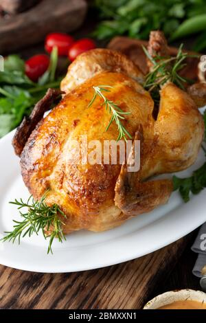 Ganze gebratene Hähnchen auf weißem Teller mit Rosmarin, Saucen und Gemüse. - Stockfoto