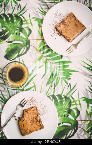 Draufsicht auf eine Tasse Kaffee und zwei Dessertteller mit Brownie-Kuchen über Tischdecke mit grünen Blättern Muster. - Stockfoto
