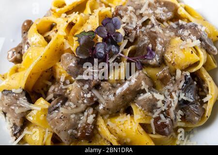 Frische Pappardelle Pasta mit Steinpilzen und Trüffelduft. Traditionelles italienisches Gericht im italienischen Stil und mit Gewürzen zubereitet. Parmesan und Mozzarella - Stockfoto