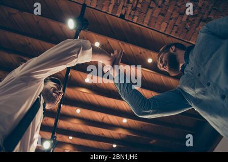Low-Winkel-Foto von Stylisten geben High Five zu seinem Freund Client im Retro-Stil Loft Friseur Shop mit Lichtern an der Decke. Junger Mann kam zu - Stockfoto