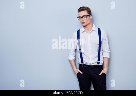 Portrait des attraktiven nachdenklichen jungen Mannes in weißem Hemd und Brille, auf dem reinen hellen Hintergrund stehend und mit violetten Hosenträger - Stockfoto