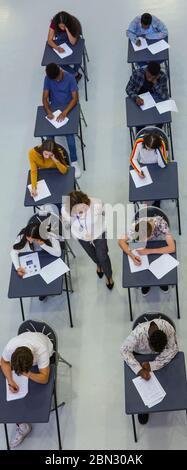 High School Lehrer beaufsichtigt Schüler, die Prüfung an Schreibtischen - Stockfoto