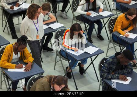 High School Lehrer Überwachung der Schüler, die Prüfung an Tischen - Stockfoto
