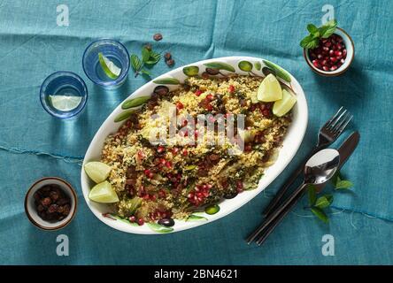 Couscous wird auf Orangensaft mit gekochtem Gemüse, karamellisierten Zwiebeln, Rosinen und Granatapfelkernen gekocht. Auf dem Tisch mit einer Leinentischdecke - Stockfoto