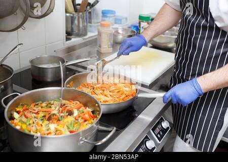 Mann in Schürze und Handschuhe Kochen frisches Gemüse für gesunde Ernährung - Stockfoto