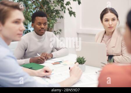 Multiethnische Gruppe von Geschäftsleuten, die während der Arbeit am Treffpunkt über das Projekt diskutieren, konzentrieren sich auf afroamerikanische Menschen, die intensiv p hören - Stockfoto