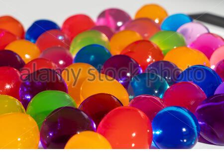 Nahaufnahme einer großen Gruppe von bunten großen Polymer-Wasserbälle, die wachsen, wenn Sie sie auf Wasser während ein paar Stunden auf einer weißen Oberfläche wo tauchen - Stockfoto