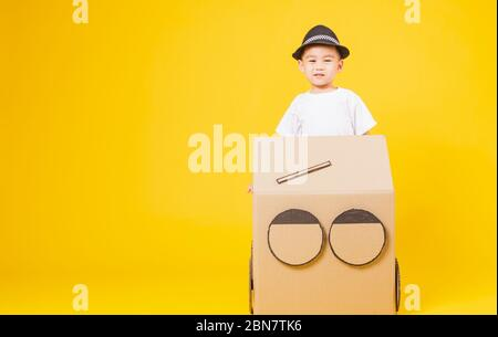 Portrait fröhliche asiatische süße kleine Kinder Junge lächeln so glücklich mit weißem T-Shirt tragen Auto kreativ durch Pappe fahren, Studio auf gelbem Hintergrund gedreht - Stockfoto