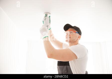Elektriker Arbeiter Montage elektrische Lampen in neue Wohnung - Stockfoto