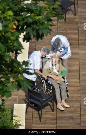 Krankenschwestern, die an einem sonnigen Tag während der Coronavirus-Pandemie Covid-19 eine ältere und behinderte Frau in einem Pflegeheim betreuen. Die Betreuer tragen eine Gesichtsmaske. - Stockfoto