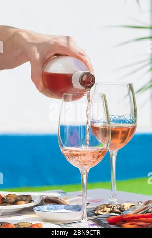 Eine Hand der Frau, die Roséwein ausgießt - Stockfoto