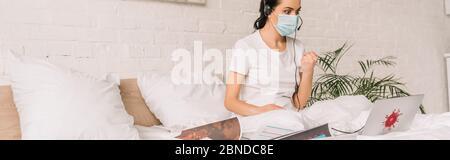 Panoramabild eines wütenden Fernbedieners im Headset und einer medizinischen Maske, die im Bett arbeitet und während eines Videoanrufs Faust zeigt - Stockfoto