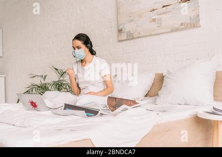 Wütender Fernbediener in medizinischer Maske und Headset, der im Bett arbeitet und beim Videoanruf Faust zeigt - Stockfoto
