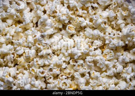 Eine Streuung von gekochtem Popcorn. Blick von oben. Hintergrund. - Stockfoto