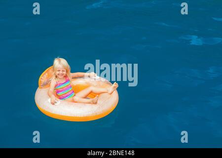 Foto von glücklichen Kind Schwimmen mit Spaß auf aufblasbaren Schwimmring im Meerwasserpool. Familienreisen Lifestyle, Kinder, Eltern Outdoor-Schwimmen Aktivität - Stockfoto