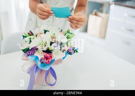 Frau liest Karte in Blumenstrauß von Freund in Geschenkbox auf der Küche zu Hause gelassen. Überraschungsgeschenk - Stockfoto