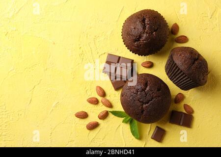Leckere Muffins, Schokolade und Mandel auf gelbem Hintergrund - Stockfoto