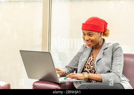 Schöne junge afrikanische muslimische Geschäftsfrau lächelnd, während sie ihren Laptop-Computer - Stockfoto
