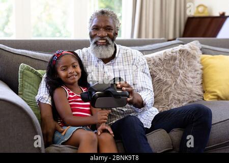 Älterer afroamerikanischer Mann und seine Enkelin mit vr-Headset - Stockfoto