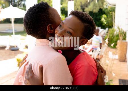 Ältere afroamerikanische Frau umarmen mit ihrer Tochter während eines Familienmittagessen im Garten Stockfoto