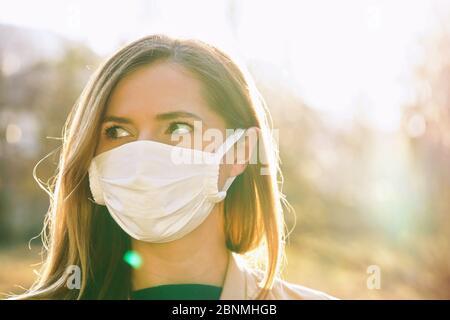 Junge Frau trägt weiße Baumwolle Virus Mund Nase Maske, schöne Hintergrundbeleuchtung Sonne Bokeh im Hintergrund, Nahaufnahme Gesicht Porträt - Stockfoto