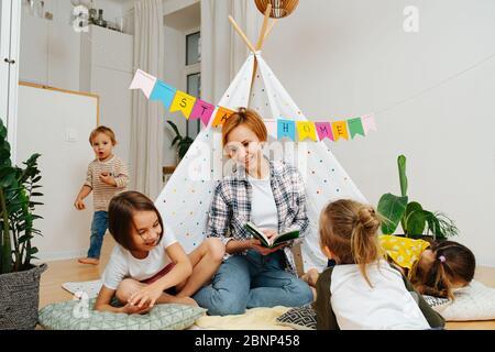 Schöne junge Mutter liest Schlafenszeit Geschichte für Kinder in einer Hütte zu Hause - Stockfoto
