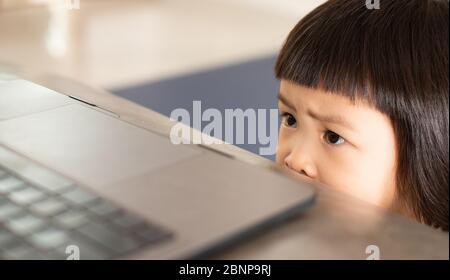 Asiatische Mädchen beobachten eine unheimlich Cartoon online von einem Notebook-Computer, die einen Gesichtsausdruck und einen hellen Ausdruck von Angst und Sorge hat. - Stockfoto