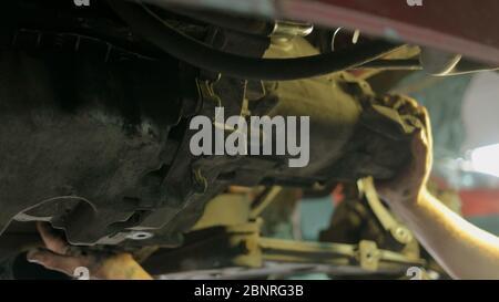 Arbeiter Mechaniker Abschrauben Teile des unteren Teils des Autos unter angehobenen Auto. - Stockfoto